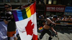 "A man holds a rainbow colored Canadian flag attached to a hockey stick during the ""WorldPride"" gay pride Parade in Toronto"