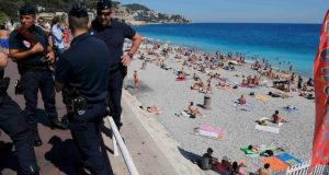 French CRS police patrol on the walkway above a public beach after the Bastille Day truck attack