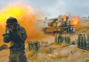 An Israeli soldier stands near a mobile artillery unit as it fires a shell into southern Lebanon