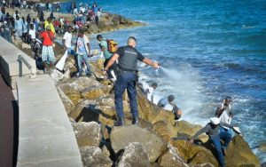 Migrants are pushed back by French police as they try to cross the France-Italy border by sea