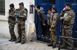 Students peering out from a doorway as armed soldiers patrol outside their school in the Jewish quarter of the Marais district in Paris, Jan. 13, 2015