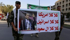 Members of Hashid Shaabi hold a banner of Abdul-Malik al-Houthi during a demonstration to show support for Yemen's Shiite Houthis and in protest of an air campaign in Yemen by a Saudi-led coalition, in Baghdad, March 31, 2015