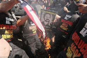Bilingual burning: The Communist agitators wore t-shirts demanding revolution in both English and Spanish as they tried to desecrate Old Glory