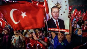 Pro-Erdogan supporters hold Turkish national flags and a portrait of Turkish President Recep Tayyip Erdogan during a rally against the military coup on Taksim square in Istanbul on July 23, 2016.
