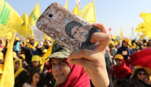 A Hezbollah supporter shows off a picture of Lebanon's Hezbollah leader Sayyed Hassan Nasrallah on her phone during a rally marking the 10th anniversary of the end of Hezbollah's 2006 war with Israel