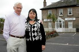 Hazelmary and Peter Bull with their home