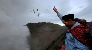 A Hindu worshipper throws offerings into the volcanic crater of Mount Bromo as smoke and ash rise from the volcano during the Kasada ceremony in Probolinggo, Indonesia
