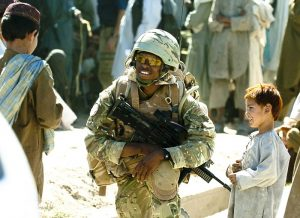 A Royal Marine of 40 Commando (40 Cdo) talks with local children during a foot patrol in Sangin, Afghanistan.