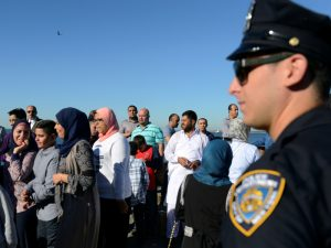 A member of the New York City police department stands guard during a group prayer session for the Muslim holiday Eid al-Adha in the Brooklyn borough of New York City, on August 12, 2016. Photo courtesy of Reuters/Stephanie Keith