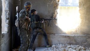 Rebel fighters fire toward regime forces on the southwestern edges of Aleppo
