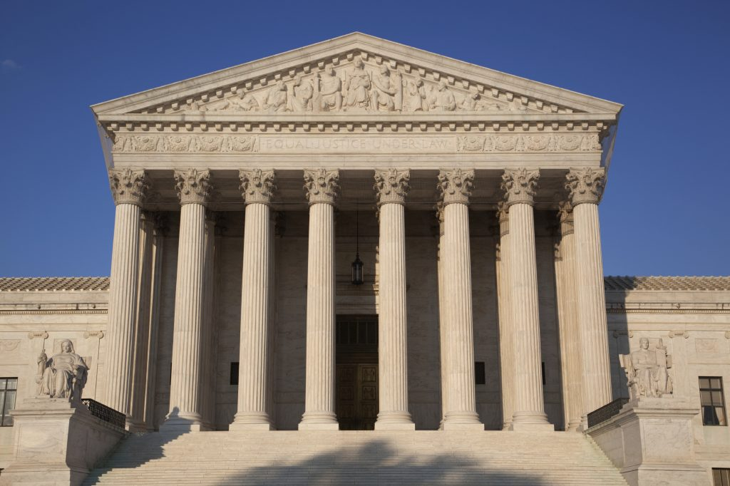United States Supreme Court Building in Washington, DC, in golden light of late afternoon, against a clear blue sky
